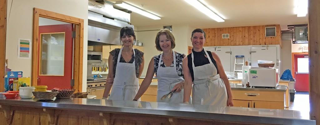 Volunteer cooks smile after serving up a meal