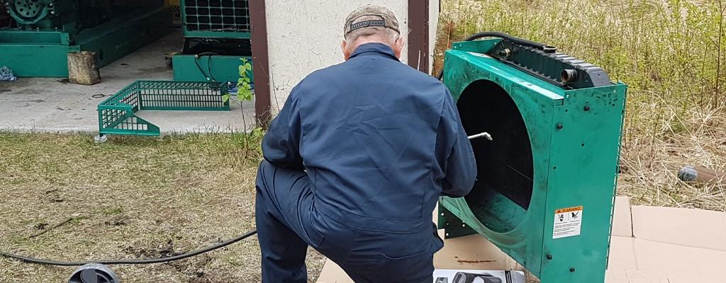 a volunteer mechanic works on a diesel generator